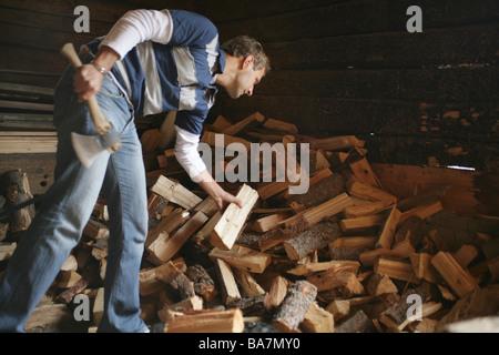 Man chopping wood on alp, Heiligenblut, Hohe Tauern National Park, Carinthia, Austria - Stock Photo