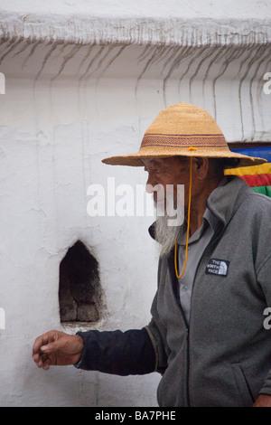 Man Pilgrim at Kathmandu Boudhanath praying by statue and prayer mills. Nepal Asia 90415 Nepal - Stock Photo