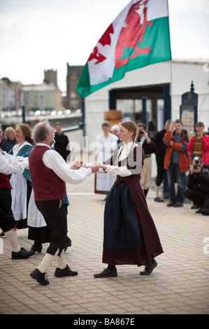 Traditional welsh folk dancing on the promenade Aberystwyth Ceredigion Wales UK with red dragon banner in background - Stock Photo