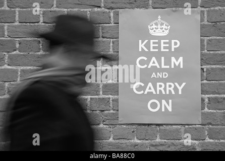 A man walking past a Second World War poster urging people to keep calm and carry on. - Stock Photo