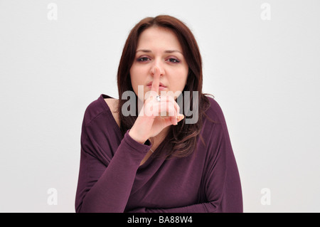 Young woman holding finger up to mouth - Stock Photo