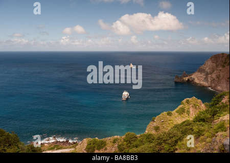 Super yacht Big Aron at anchor in Wells Bay from the road above on Saba with Diamond Rock behind - Stock Photo