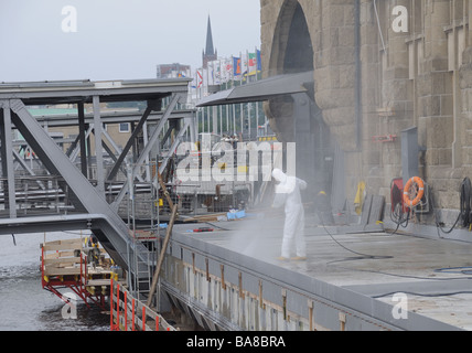 Workman cleaning a quai in the harbour of Hamburg, Germany. - Stock Photo