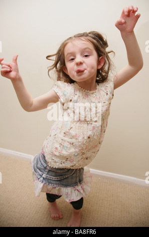 Hyperactive child jumping around and poking out her tongue - Stock Photo