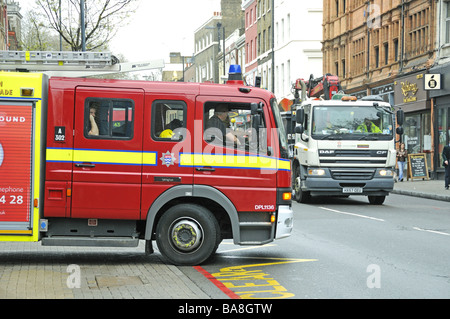 Fire engine leaving it's station and edging into Upper Street in front of a lorry Islington London UK - Stock Photo