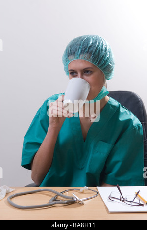 Doctor sat in office drinking coffee - Stock Photo