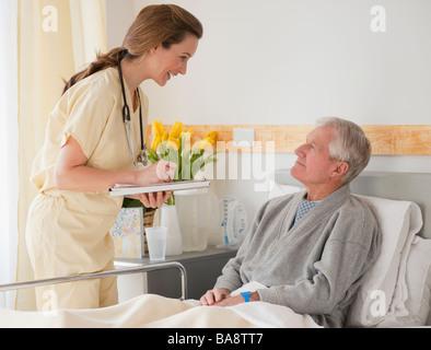 Nurse caring for senior man in hospital - Stock Photo