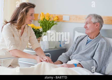 Daughter visiting senior father in hospital - Stock Photo