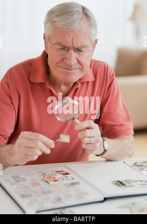 Senior man looking at stamp collection - Stock Photo