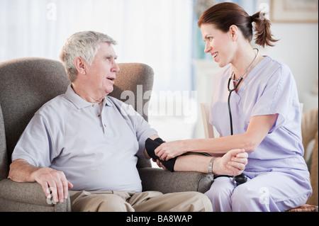Nurse taking senior man's blood pressure - Stock Photo