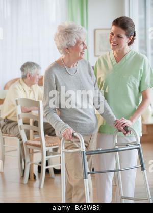 Nurse helping senior woman in walker