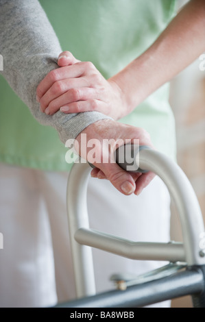 Nurse helping senior woman in walker - Stock Photo