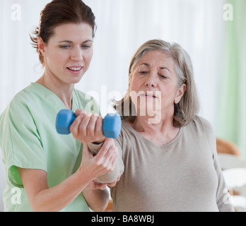Physical therapist helping senior woman - Stock Photo