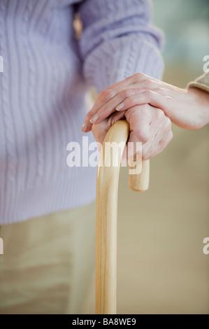 Close up of senior woman holding cane