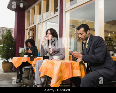 Businesspeople using cell phones at outdoor cafe - Stock Photo