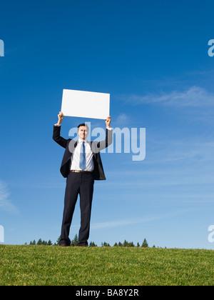Businessman holding blank sign - Stock Photo