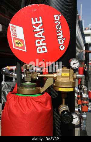 pressured gas bottle and lollypop in Ferrari Box at racetrack at Formula One testing sessions - Stock Photo
