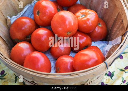 Tomatoes in a basket at a fruit stand - Stock Photo