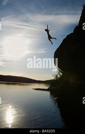 A man jumping from a cliff Sweden - Stock Photo