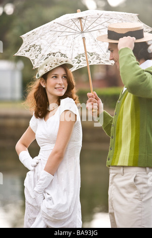 Portrait of 1920s socialite couple relaxing at garden party on water's edge - Stock Photo
