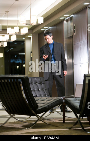 Asian businessman waiting in building lobby - Stock Photo