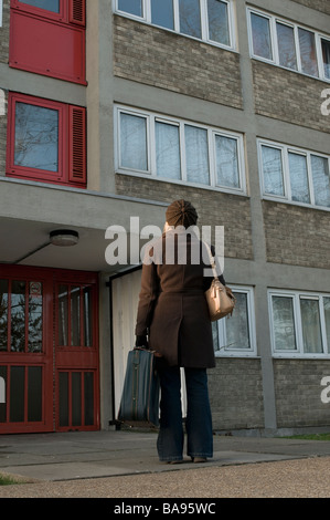 lady standing outside a block of council flats with suitcase - Stock Photo