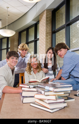 Teenage students hanging out in library with books - Stock Photo