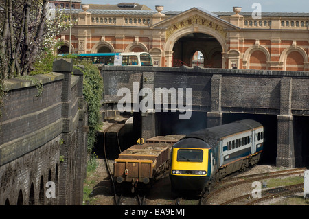 A freight train going under a bridge as a passenger train emerges and a bus is seen on the road above - Stock Photo