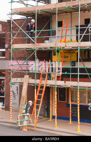 Two scaffolders at work in the uk erecting scaffolding - Stock Photo