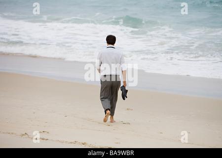 A Scandinavian man walking on the beach, Brazil. - Stock Photo