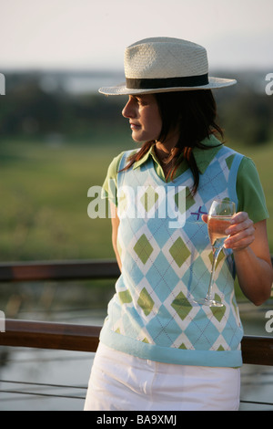 A Scandinavian woman wearing a hat holding a glass of wine, Italy. - Stock Photo