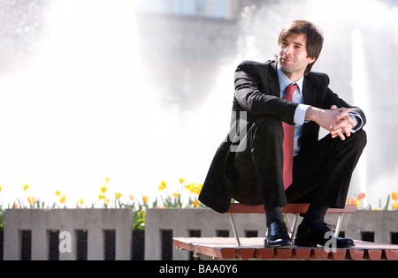 Businessman sitting in front of a fountain, Stockholm, Sweden. - Stock Photo