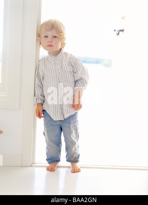A girl standing in a doorway, Sweden. - Stock Photo