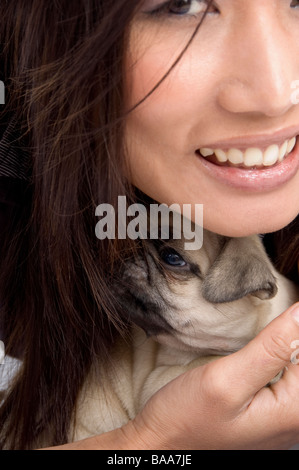 pretty woman holding puppy - Stock Photo