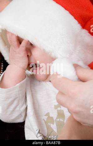 crying baby with christmas hat - Stock Photo