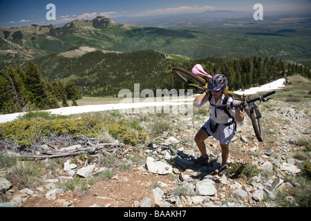 Woman carrying her bike on her shoulders in the Abajo Mountains near Montecello, Utah. - Stock Photo