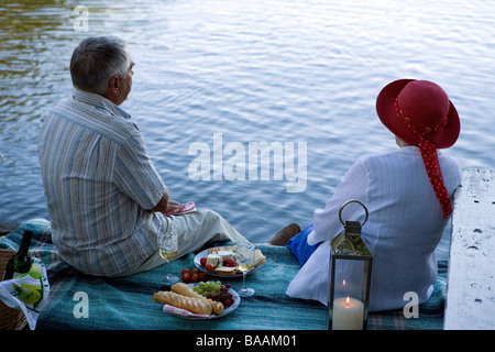 A senior couple sitting on a jetty, Sweden. - Stock Photo