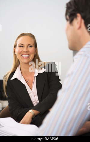 A smiling woman in an office. - Stock Photo