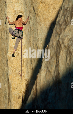 Female rock climber clings to the side of cliff. - Stock Photo