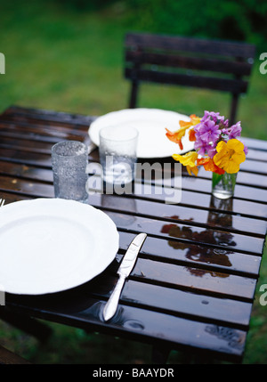 Raining on a table ready laid, Sweden. - Stock Photo