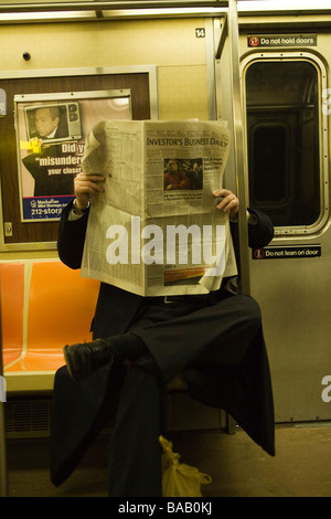 Man reads the Investors Daily Newspaper on a subway train in NYC to keep up on the world financial meltdown - Stock Photo