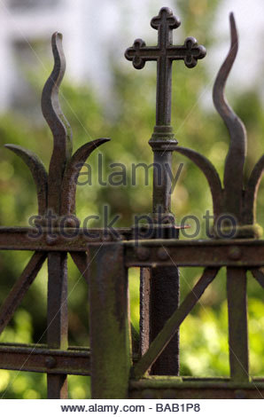 Old iron cross on a fence, grave yard in Berlin - Stock Photo