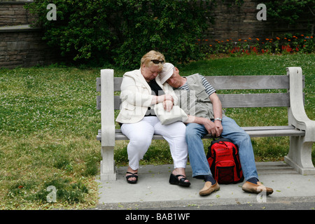 Older couple take a cat nap on a bench at the Brooklyn Botanic Gardens in Brooklyn NY - Stock Photo