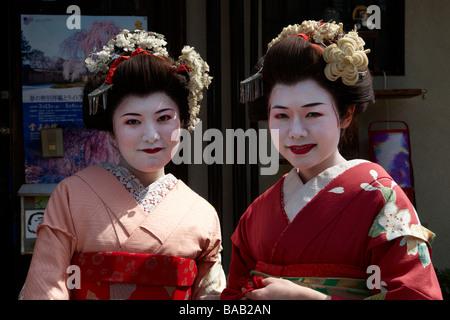 Two Maiko (trainee Geisha) pose for the camera in Kyoto, Kansai, Japan - Stock Photo
