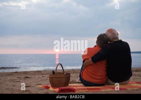 An elderly couple sitting on a beach, Skane, Sweden. - Stock Photo