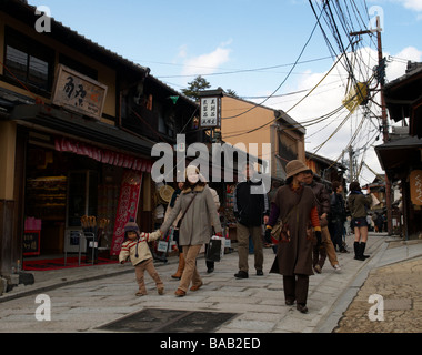 Tourists walk along Ninen-zaka - a quaint street in Kyoto, Japan lined with old wooden houses, shops and restaurants. - Stock Photo