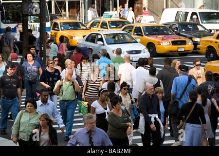 42nd Street and Fifth Avenue is constantly clogged with pedestrians buses cabs and cars at the afternoon rush hour - Stock Photo