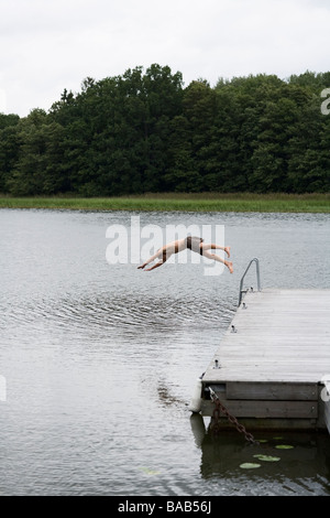 A man diving into the water, Sweden. - Stock Photo