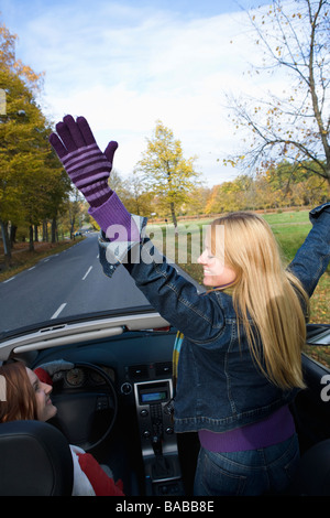 Two young women driving a cabriolet an autumn day Sweden. - Stock Photo