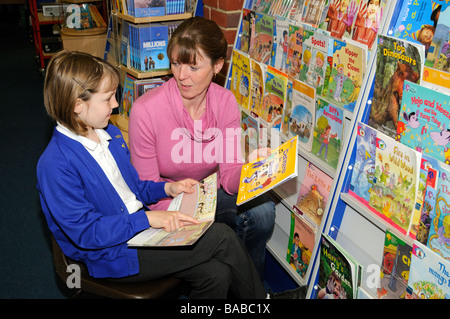 Schoolgirl with female teacher in a school library - Stock Photo